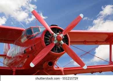 Close up view of red airplane biplane with piston engine and propeller on cloudy sky background