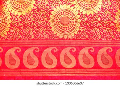 Close view of a red Banarasi silk sari. These exquisite, expensive sarees are famous for their gold and silver zari, brocade. Paisley design on the border.
