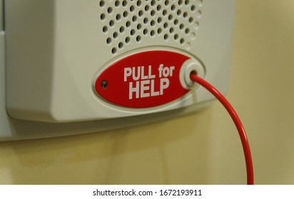Close view of a red cord and button that can be pulled in case of an emergency, located in a private bathroom in a hospital