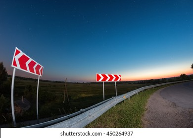Close view of red road signs at night with dark deep starry night at the background
