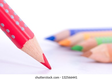 Close up view of red standing pencil in front of colorful illustration pencils, isolated on white background.