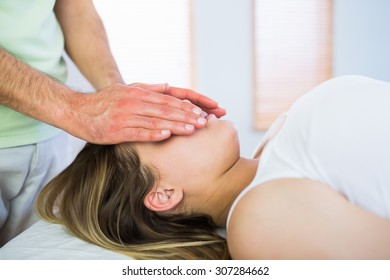 Close up view of relaxed pregnant woman getting reiki treatment in a studio