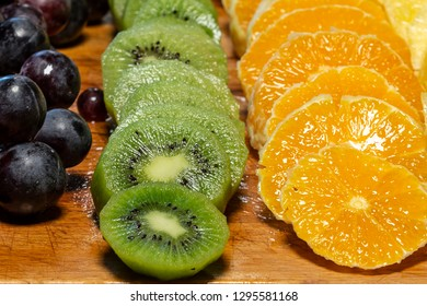 Close view of rings of sliced kiwi, orange and grape fruits on a wooden desk