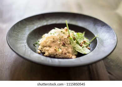 Close up view at risotto with gem fit and lovage celery on a wood table