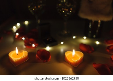 Close up view of a romantic dinner table with glasses of wine, roses, candles and a engagement ring. Focus on the candles