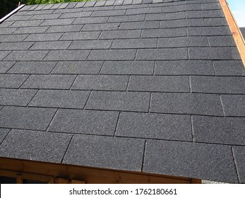 Close up view of a roof with  black bitumen shingles real estate construction background image