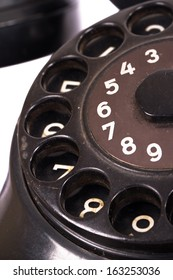 Close up view, rotary dial of black vintage phone, isolated on white background.