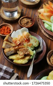 Close Up View of Rujak Buah, or Fruity Rojak. Indonesia Local Food, Made from Fresh Fruit and Fried Tofu, Served with Palm Sugar and Peanut Sauce. Garnished with Fried Garlic.