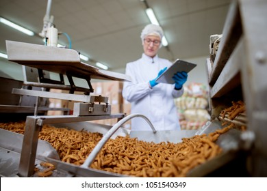 Close up view of a salt stick snacks being processed through a production line in food factory while being inspected by a female young worker with a tablet in a sterile cloth.