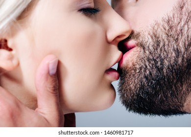 close up view of sensual couple kissing isolated on grey