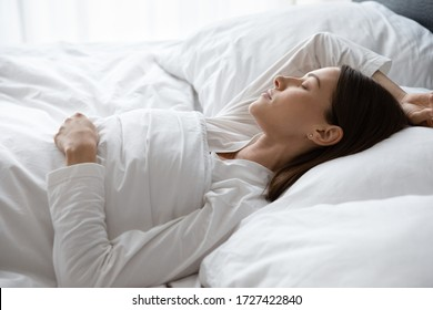 Close up view serene 30s woman sleeping covered with soft warm duvet lying on back in comfortable mattress bed enjoy soft fresh bedclothes, enough rest for body photo in early morning time to wake up