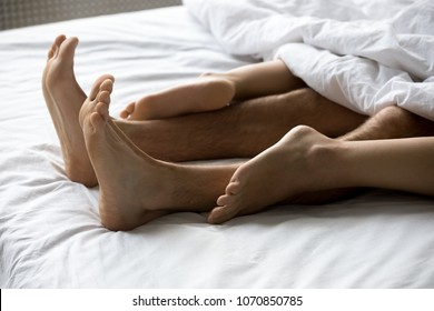 Close up view of sexy romantic couple feet touching making love in bed concept, male and female legs of lovers lying on white sheets having sex or relaxing enjoying intimacy in woman on top position