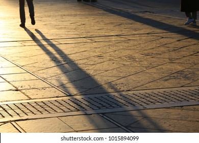 Close up view of shadows of people walking on an urban paved place. Silhouettes of the people on the pavement with feet and legs. Lengthened human forms on the grey stone floor. Abstract picture.