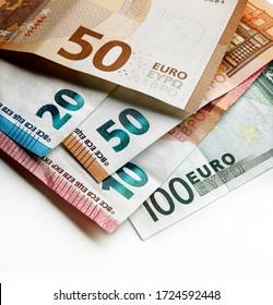 Schließen Sie die Ansicht. Langsame Fokussierung auf einen Haufen gebrauchter Euro-Banknoten mit unterschiedlichen Werten mit einem Spot-Lichteffekt