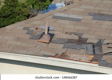 A close up view of shingles being blown off a roof and other roof damage