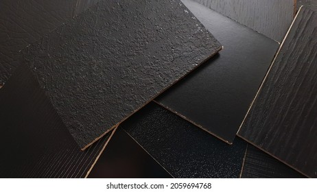 close up view showing multi surface of melamine samples contains wooden, stone, leather, matt, peel, peal textures in black color for selection. furniture particle board structure samples.