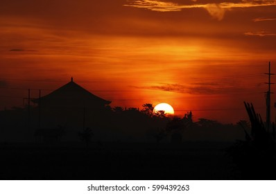 Close view of silhouettes of a house with a traditional balinese roof, a pole with cables and a bright red sunset, Bali island, Indonesia, for travel themes and ads