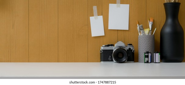 Close up view of simple workspace with camera, painting brush, vases and copy space on white table with notepad on plank wall