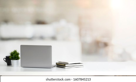 Close up view of simple workspace with laptop, notebooks, coffee cup and tree pot on white table with blurred office room background - Shutterstock ID 1607845213