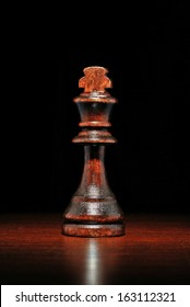 Close up view of a single illuminated wooden king chess piece on a reflective wooden surface against a dark background