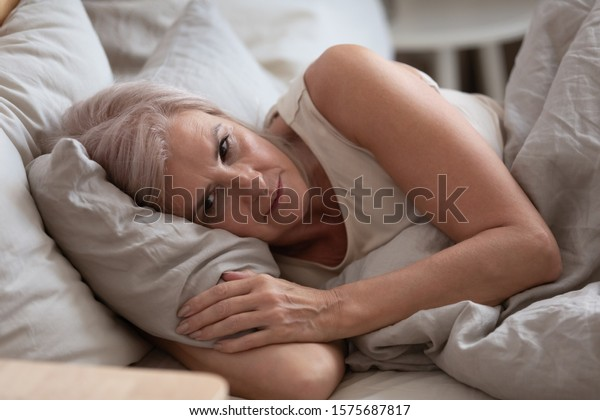 Close up view sleepless middle-aged woman lying in bed suffers from insomnia sleep disorder cant sleep till morning, depressed elderly female looking upset thinking about life, health troubles concept