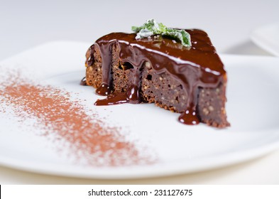 Close up view of a slice of freshly baked chocolate tart with rich chocolate sauce dripping down the sides served on a plate for dessert