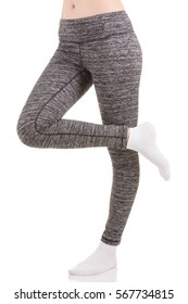 Close up view of slim woman legs from the side in grey sports thermal patterned pants standing on one leg with other leg raised in white socks on white isolated background