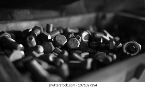 Close up view of the small metal steel nuts inside a and old metal box for tools. Blurred close up of old steel nuts and bolts in tool box