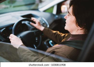 Close up view of smiling senior woman driving a car through the city.