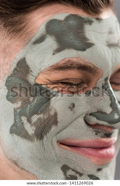 close up view of smiling young man with clay mask with closed eyes