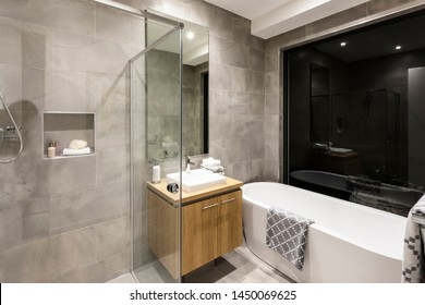 A close view of smooth curved soaking bathtub alongside a wall mounted washbasin, a wall mirror and a wooden cabinet under it.