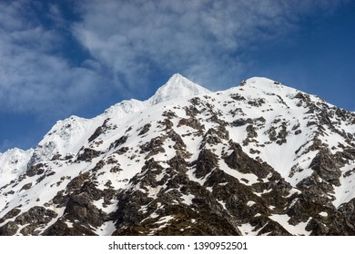 Close up view of a snowcapped mountain peak with clouds forming around it as seen from the Hooker Valley Track in the the Aoraki/Mount Cook National Park.