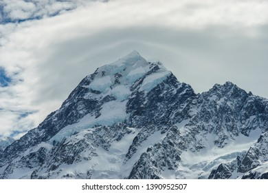 Close up view of a snowcapped mountain peak with clouds forming around it. Mount Cook - the hghest mountain of New Zealand. Hooker Valley at the Aoraki/Mount Cook National Park.