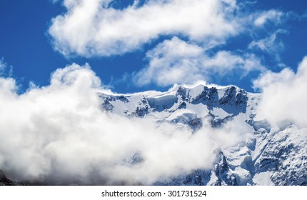 Close view of snowy mountain ridge shrouded in clouds. Blue sky. Clear summit. North Caucasus.