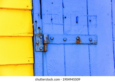 Close up view of some of the weathered blue and yellow painted boards and shutters as part the iconic bathing boxes on Brighton Beach, Brighton, VIC, Australia