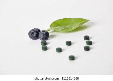 close up view of spirulina pills, blueberries and mint leaf on white background