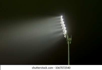 Close view of a sports stadium flood light lighting the sky on a dark night