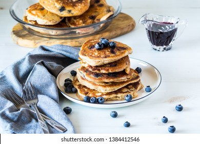 Close up view of a stack of blueberry pancakes with blueberry syrup and fresh blueberries ready for eating.