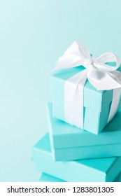 Close view the stack of boxes tied with silk ribbon, lying on each other on tiffany blue color pastel background. Best gift for girls concepts.