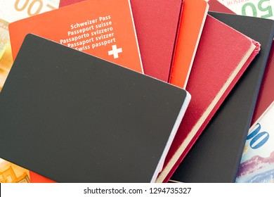 close up view of a stack of passports with a Swiss passport peeking out and Swiss franc bank notes in the background