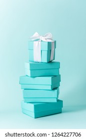 Close view the stack of Tiffany boxes tied with silk ribbon, lying on each other on tiffany blue color pastel background. Gift festive selection.
