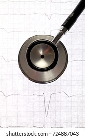 Close up view of a stethoscope on electrocardiogram background.