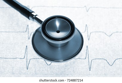 Close up view of a stethoscope on electrocardiogram background. Tinted in blue.
