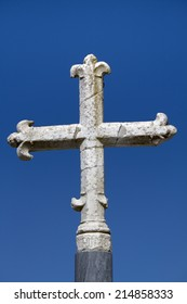 Close up view of a stone medieval cross over a blue sky.
