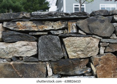 Close up view of stone wall in residential neighborhood.