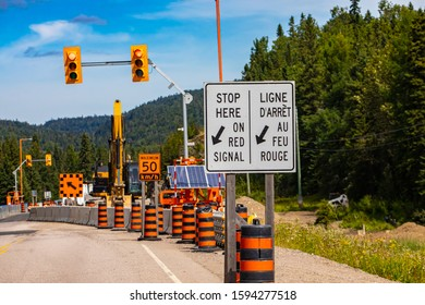 A close up view of a stop here on red signal sign in french and english, major roadworks and infrastructure improvements in Canada, with copy space
