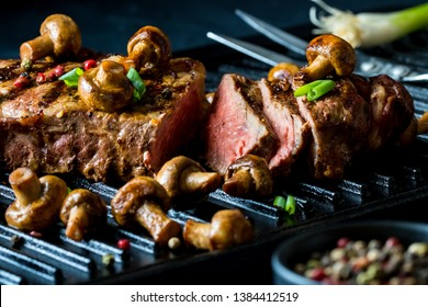 Close up view of a strip loin steak on the grill with whole button mushrooms and garnished with peppercorns and green onion.
