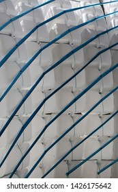 Close up view of a structure made of plastic cans. Abstract design with white bottles and blue ropes. Picture with parallel and oblique lines.