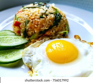 Close up view of sunny side up egg beside fried rice, served with sliced cucumber on a white plate. Nasi Goreng Kampung is a famous food in Malaysia, Singapore and Indonesia. Selective focus.