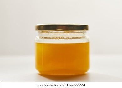 close up view of sweet organic honey in glass jar on white surface